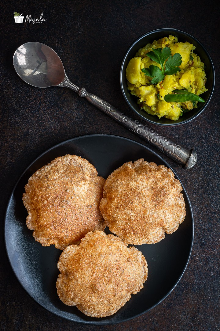 Puri on a black plated with masala on the side