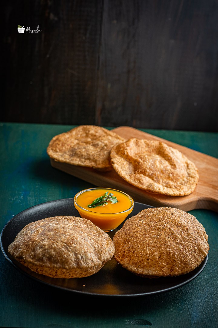 aamras poori served on a black plate.
