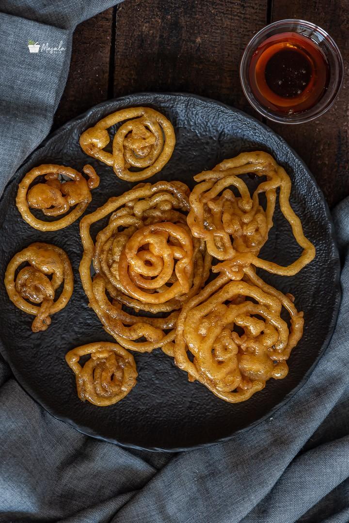 Instant Jalebi Recipe Without Yeast in jaggery syrup served on a black plate