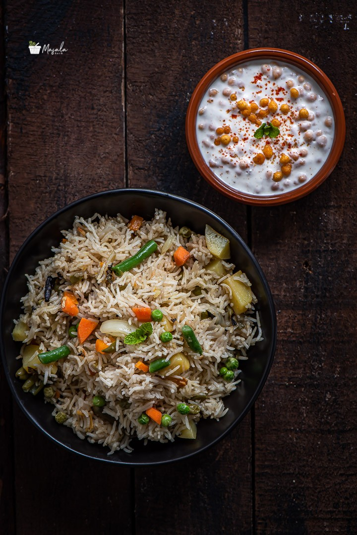 Easy Instant Pot Vegetable Biryani served in a black bowl with Boondi Raita on the side.