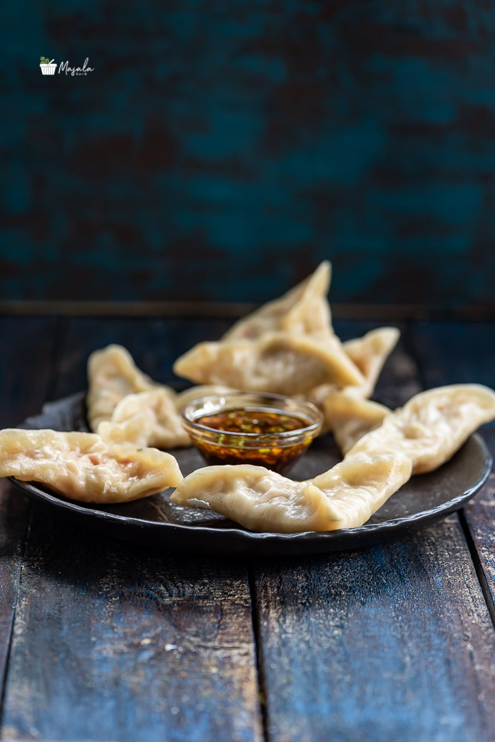 Easy Veg Momos Recipe- Steamed Veg dumplings served on a black plate with sauce.