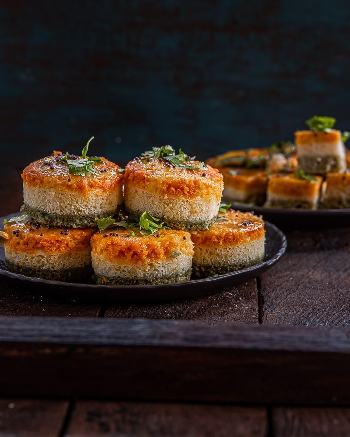 Rava Dhokla stacked on a black plate.
