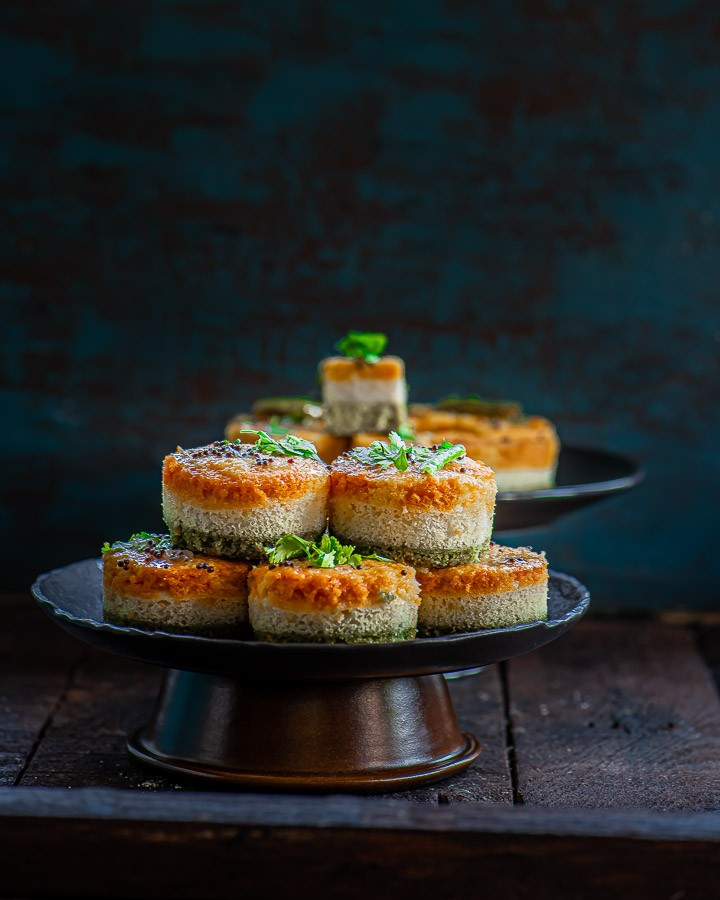 Suji Dhokla stacked on a black plate.