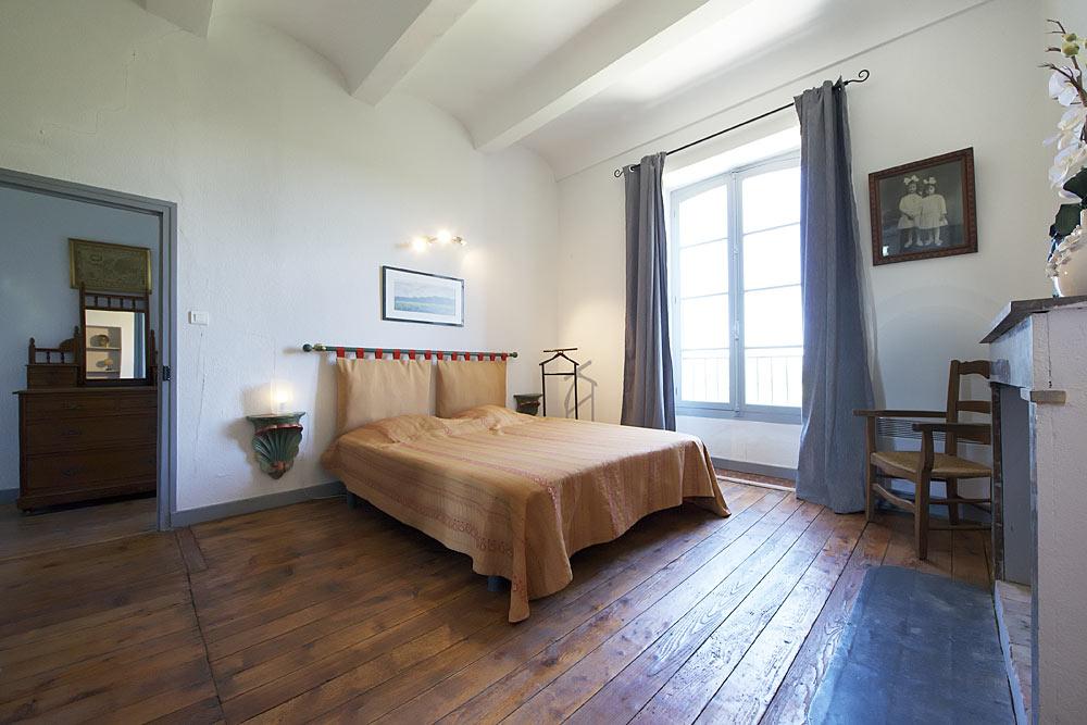 La chambre avec parquet, lit double, cheminée au premier étage au Tamaris au Mas de la Baillyde, gîtes de charme en Cévennes