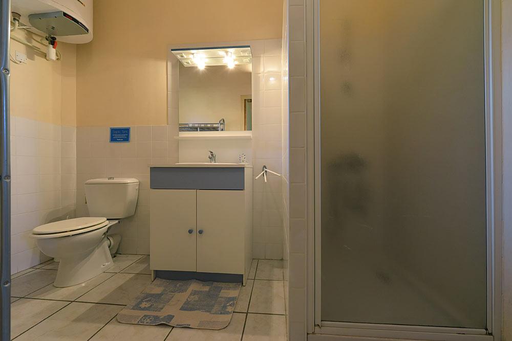 La salle de bain avec WC, lavabo et douche dans le studio Romarin au Mas de la Baillyde, gîtes de charme en Cévennes