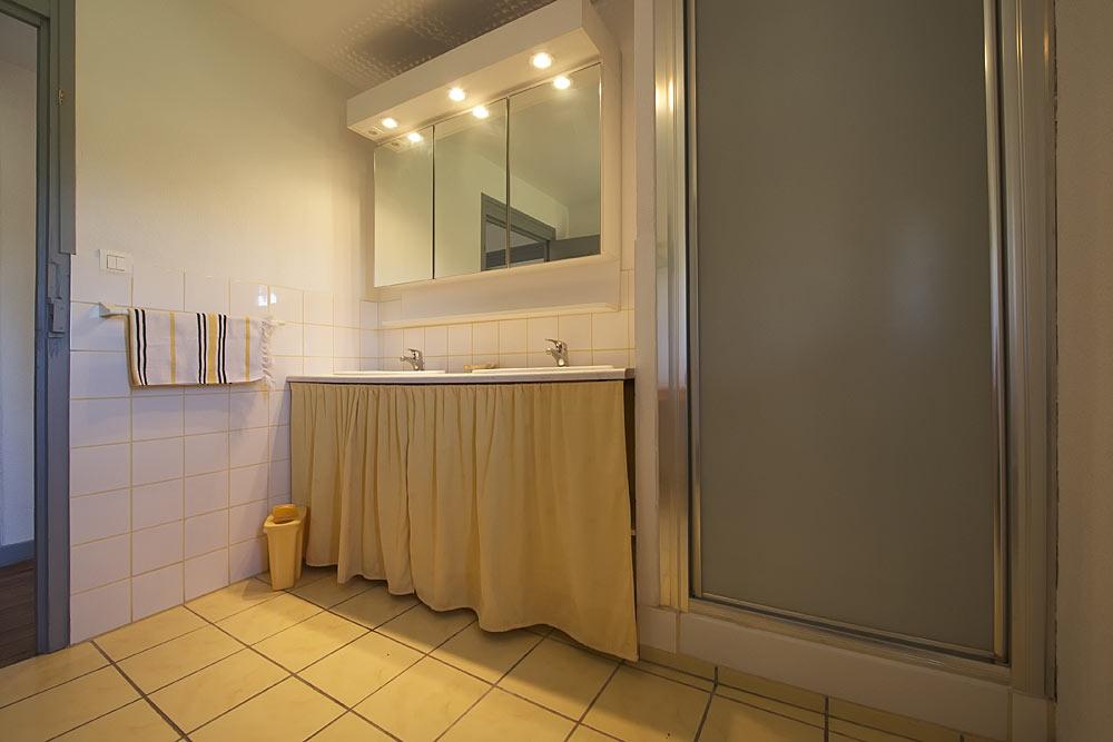 La salle de bains avec douche et lavabo double vasque au Tamaris au Mas de la Baillyde, gîtes de charme en Cévennes