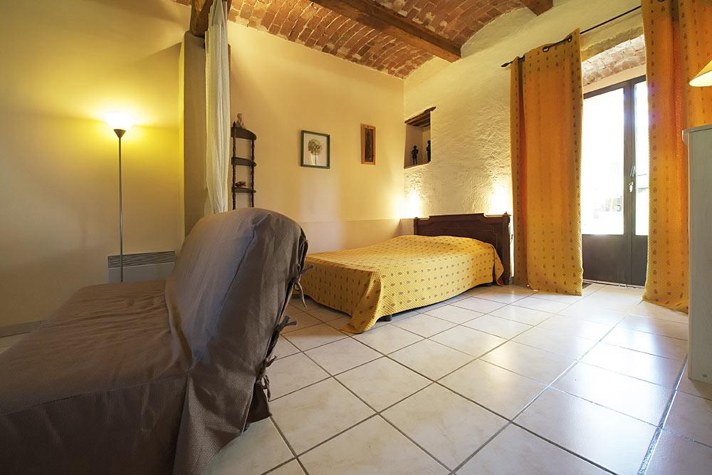 Le lit double dans le studio Romarin au Mas de la Baillyde, gîtes de charme en Cévennes