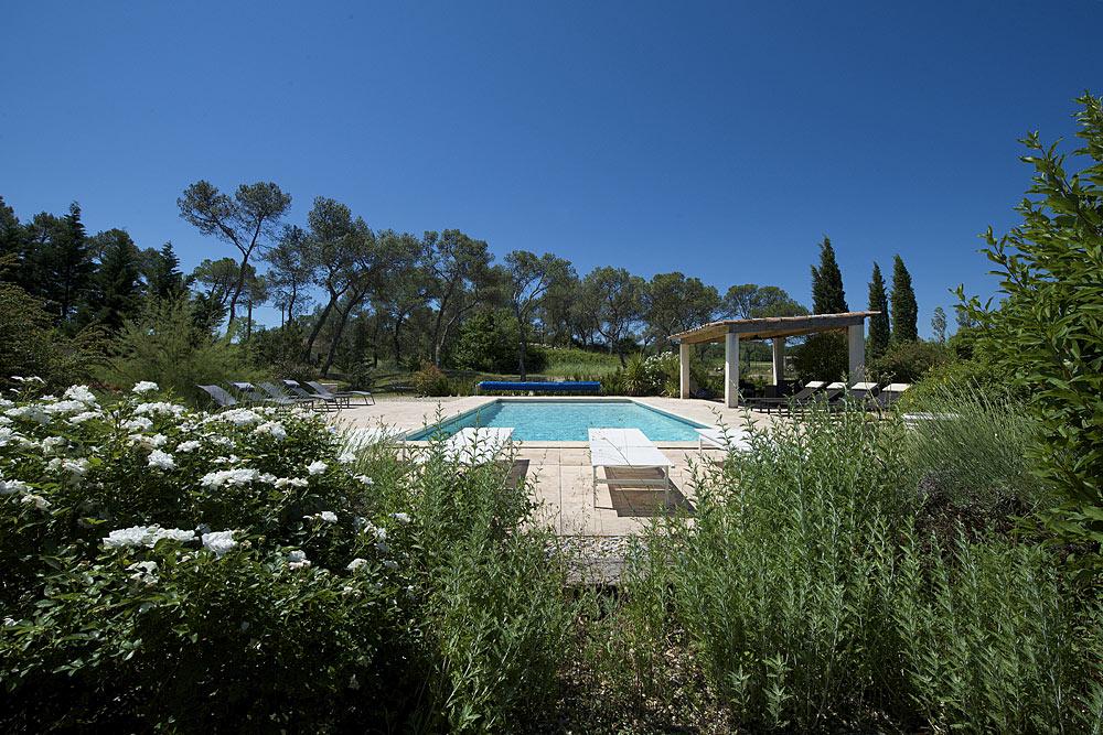 Vue de la piscine en haut des marches en bois dans les jardins au Mas de la Baillyde, gîtes de charme en Cévennes