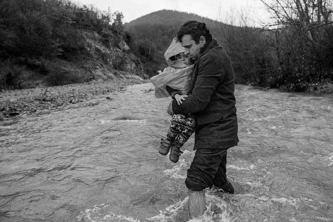James Nachtwey, Un uomo attraversa i campi al confine con la Serbia, 2015 © James Nachtwey