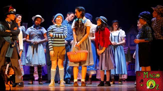 Una scena del musical Il Mago di Oz: il Sindaco e gli abitanti danno il benvenuto a Dorothy nel Paese dei Mastichini