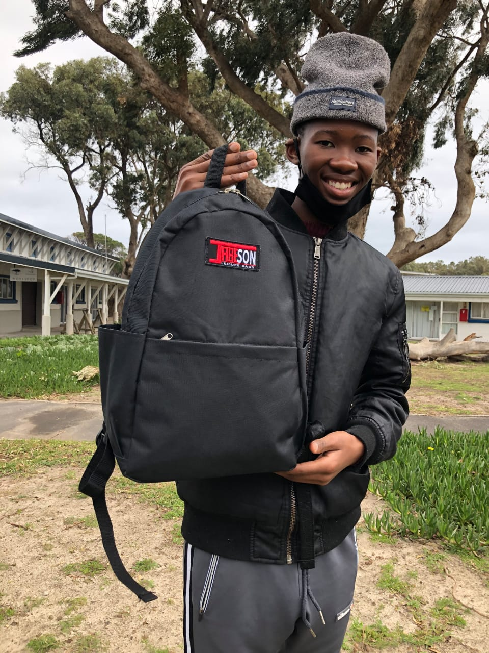 African Boy holding a bag smiling