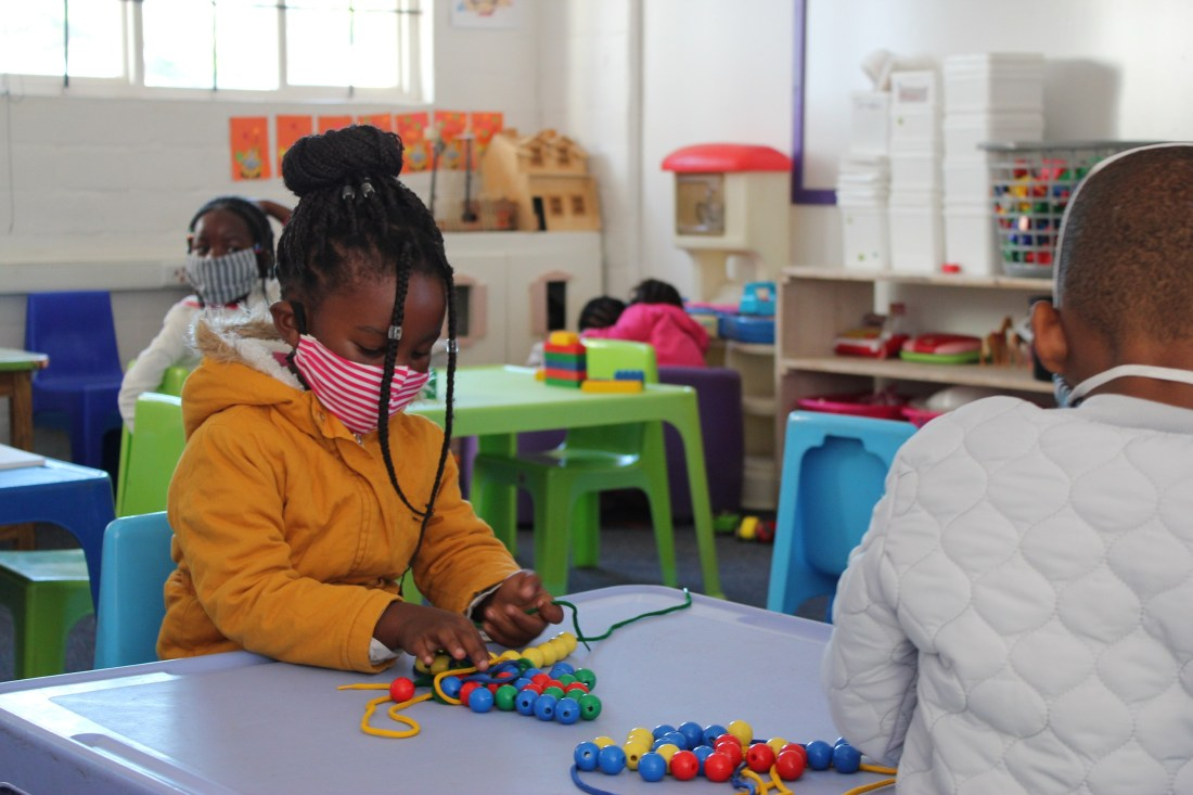 Children sitting down and playing with creative materials