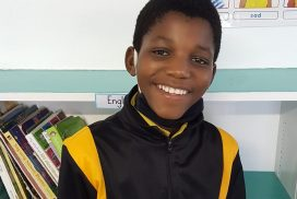1 child standing, posing in reading Centre and community upliftment programmes in Masiphumelele.