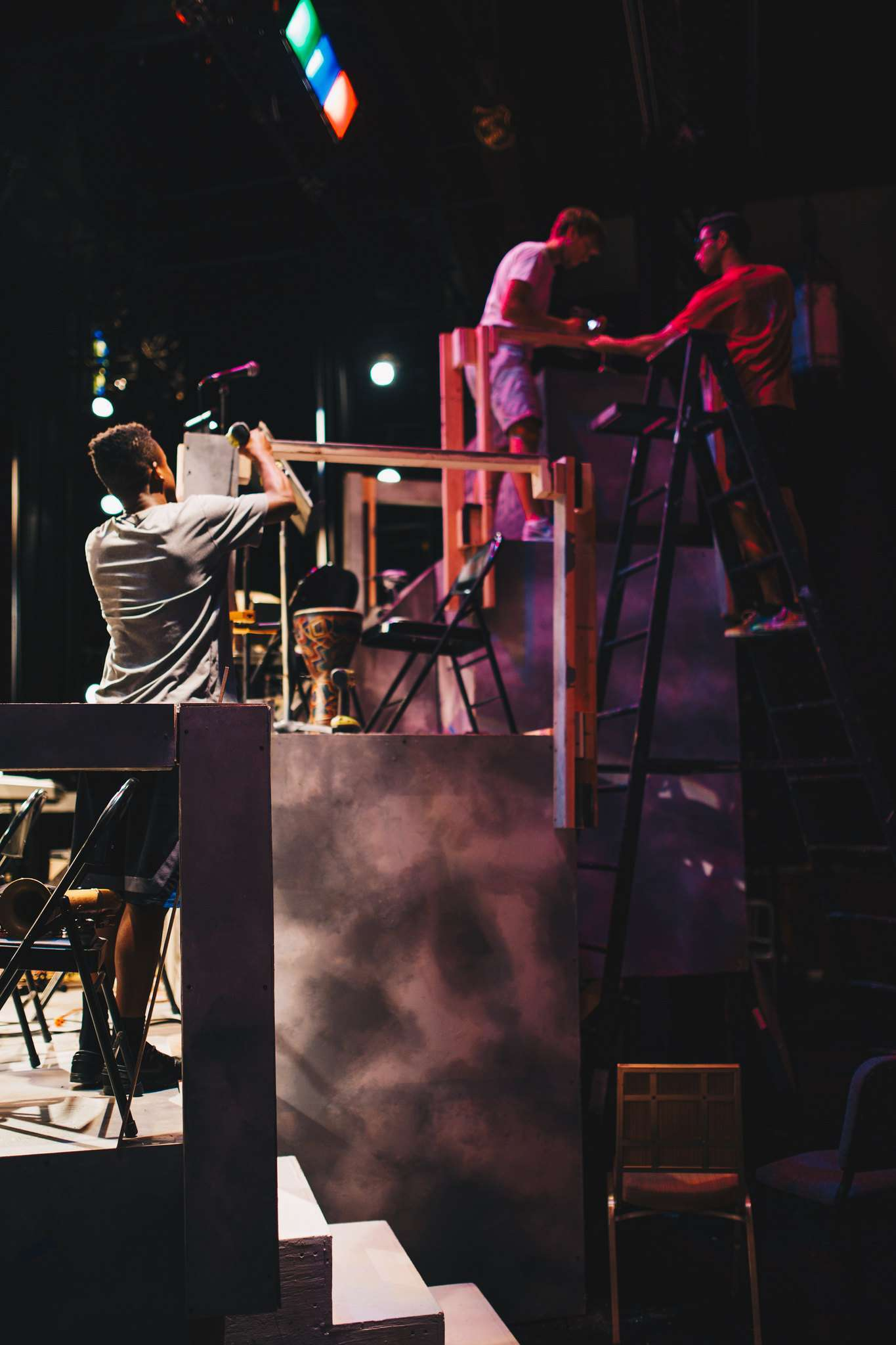 A stage crew member works on the set