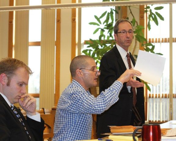 Mark McCallum holds up an exhibit as he addresses the honorable Judge Richard I. Cooper during his trial today at the Mason County Courthouse. To his right is his attorney David Glancy and to his left is Mason County Prosecuter Paul Spaniola.
