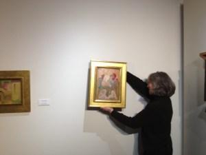 Professor of Art Rebecca Mott hangs the Dawson piece in the gallery.