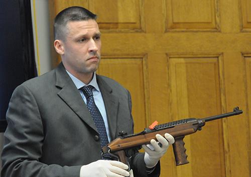 Det. Sgt. Linke shows a 30 caliber semi automatic rifle retrieved from the stolen Pontiac.