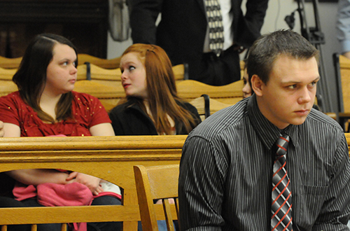 Eric Knysz awaits the beginning of testimony while members of his family are in the background.