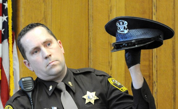 Mason County Sheriff's Chief Deputy Steve Hansen holds up MSP Trooper Paul Butterfield's garrison hat.