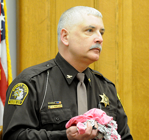 Undersheriff Jody Hartley holds the clothes he found in Sean Phillips' pocket.