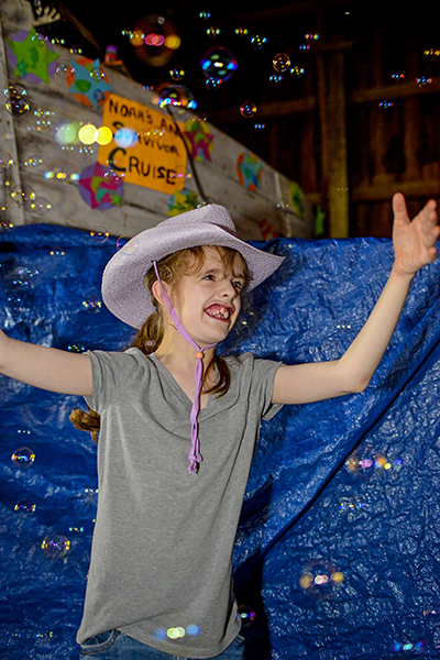 Olivia Hornsby, 12, of Manistee enjoys the bubble machine as she dances.