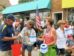 Doug Bacon accepts a fireworks contribution from a parade spectator as Michele Dolle looks on and Amy LaBarge eyes another contributor.