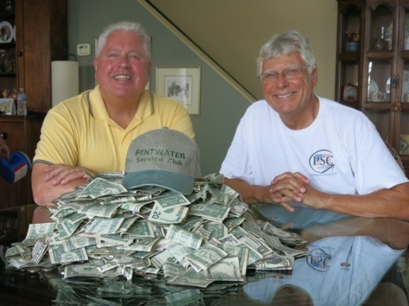 Pentwater Service Club members Kevin Dolle and Ron Beeber count the funds contributed by generous Homecoming Parade spectators – almost $3,000.