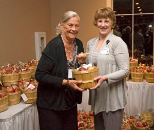 Apple crisp gifts. Top honoree Judy Thiel accepts her gift basket from hospital staff member Bonnie VanderZanden of Oceana County, who spent a good many hours washing apples and assembling gifts for the 126 hospital volunteers. The baskets also contained ingredients for making apple crisp.