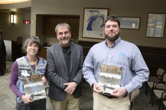 Teacher Vicki Dahringer, left, and principal Kevin Kimes, right, accept the tribe's history book from Virgil Johnson.
