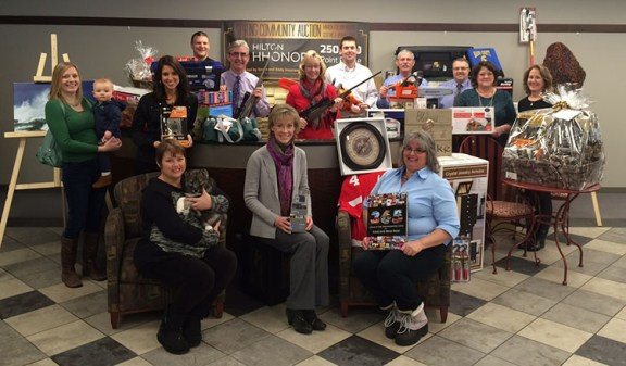 Members of the auction committee show some of the many items that will be auctioned Saturday.