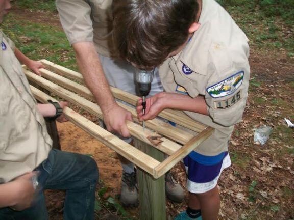 Boy Scout Stephen Boyko assembles a bench.