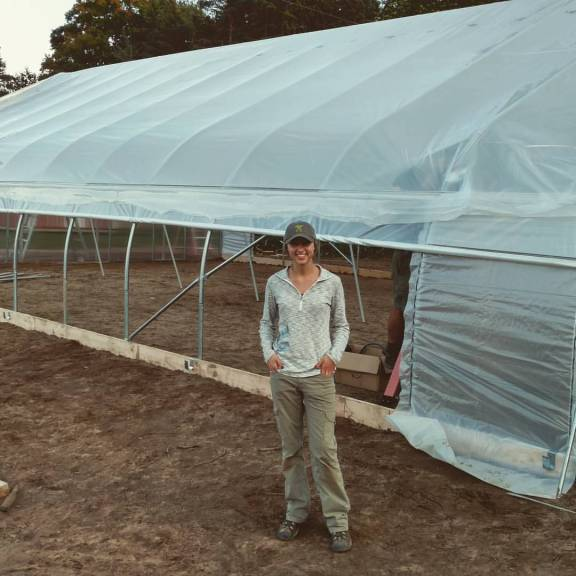 Jorhie Beadle stands in front of the new hoop house.