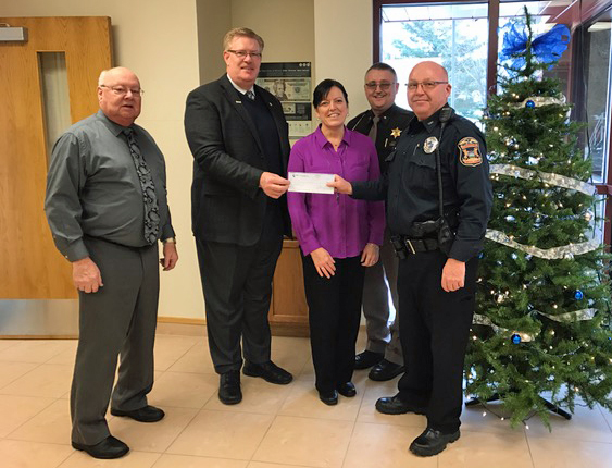 Pictured with Randy and Sherry representing the funeral home is Larry Nichols, who is also the retired Scottville Police Chief in Scottville, Tony Kuster of the Ludington Police Department and Shop with a Cop organizer, and Mason County Sheriff Kim Cole.