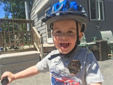 Child riding a bicycle and wearing a bicycle helmet in Tewksbury, Massachusetts