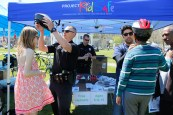 Attorney Reza Breakstone, Framingham Police and the Framingham Bicycle and Pedestrian Advisory Committee fit helmets for children at Framingham Earth Day.