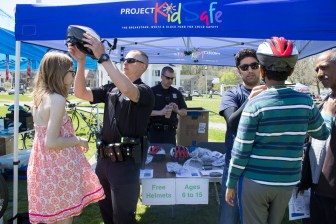 Attorney Reza Breakstone and Framingham Police fit children for helmets at the Framingham Earth Day Festival.
