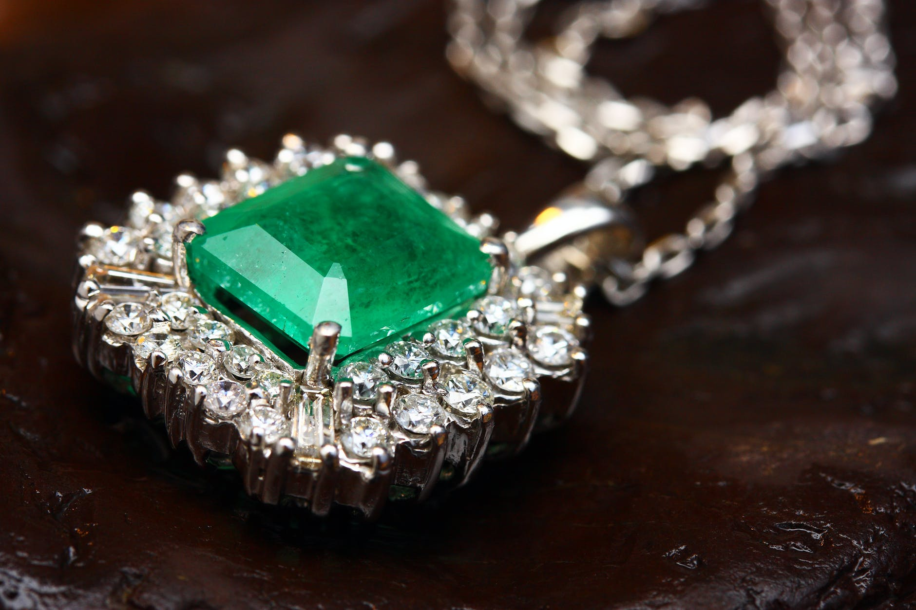 silver colored pendant with green gemstone