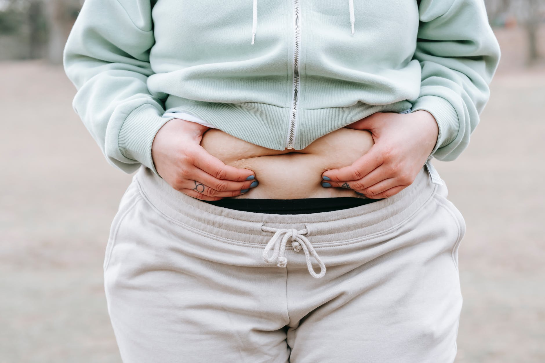 crop unrecognizable plump woman demonstrating fat on belly