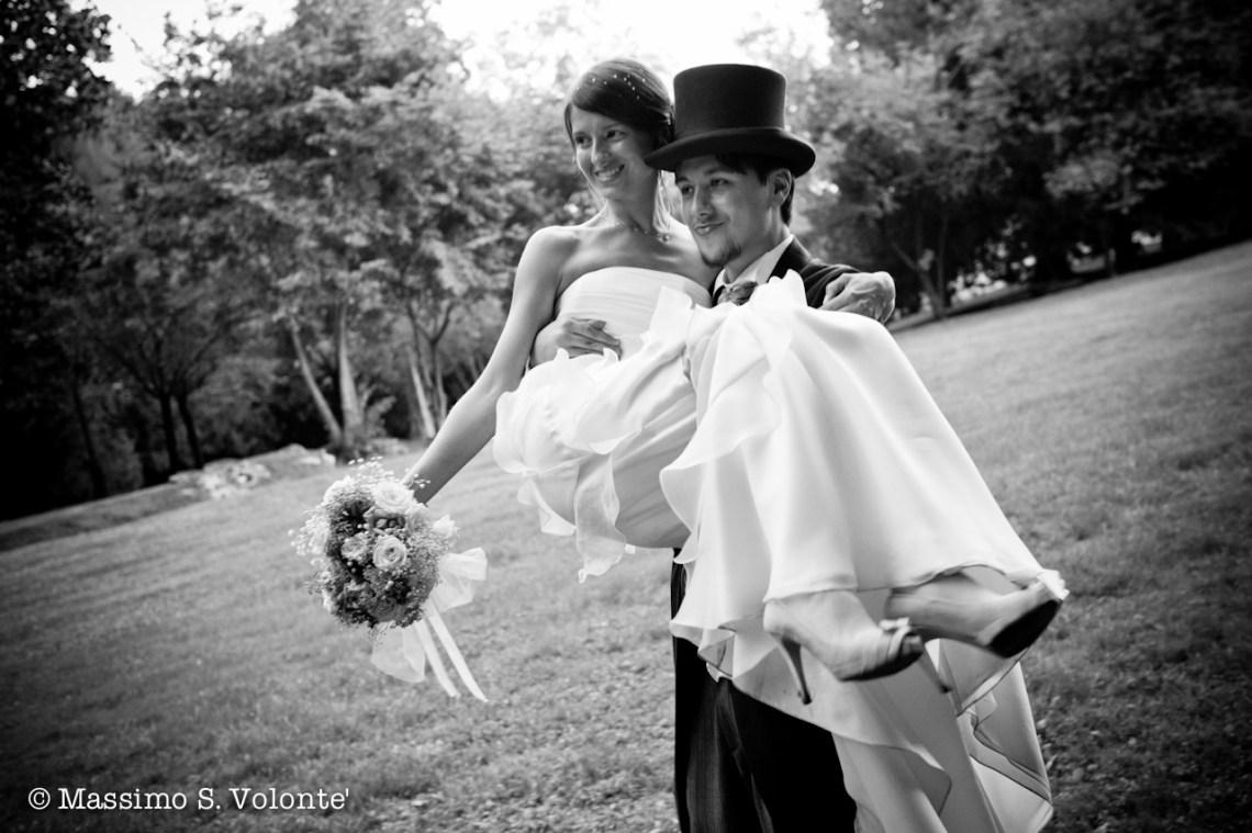 Fotografo Matrimoni Italia. Lo sposo con cappello a cilindro porta in braccio la sposa ed il suo bouquet