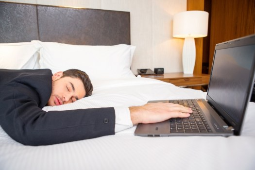 Tired and overworked. Exhausted business man in formalwear sleeping on the bed of the luxury hotel room keeping his hand on laptop keyboard