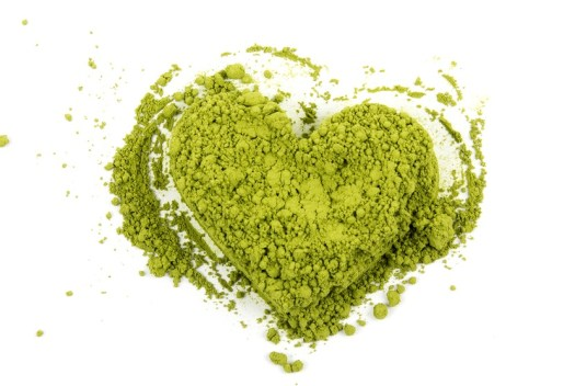 Matcha green tea in the shape of heart on white background with free space for text.