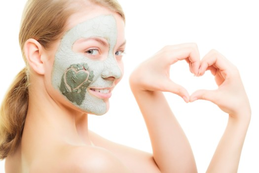 Skin care. Woman in clay mud mask on face with heart on cheek isolated on white. Girl showing symbol of love with hands. Beauty treatment.