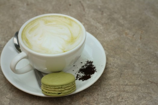 Hot green tea with macaroons at coffee shop.