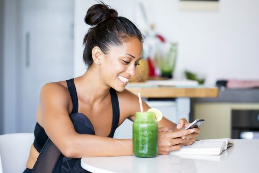 Woman drinking a homemade green detox juice, wearing sportive clothing, texting on her phone while sitting in her kitchen table