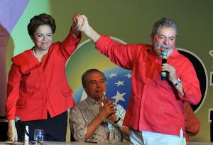 Ex president Dilma Rousseff and Lula holding hands with our current president, Michel Temer, behind. Photo Credit: Valter Campanato/Agência Brasil via Wikipedia