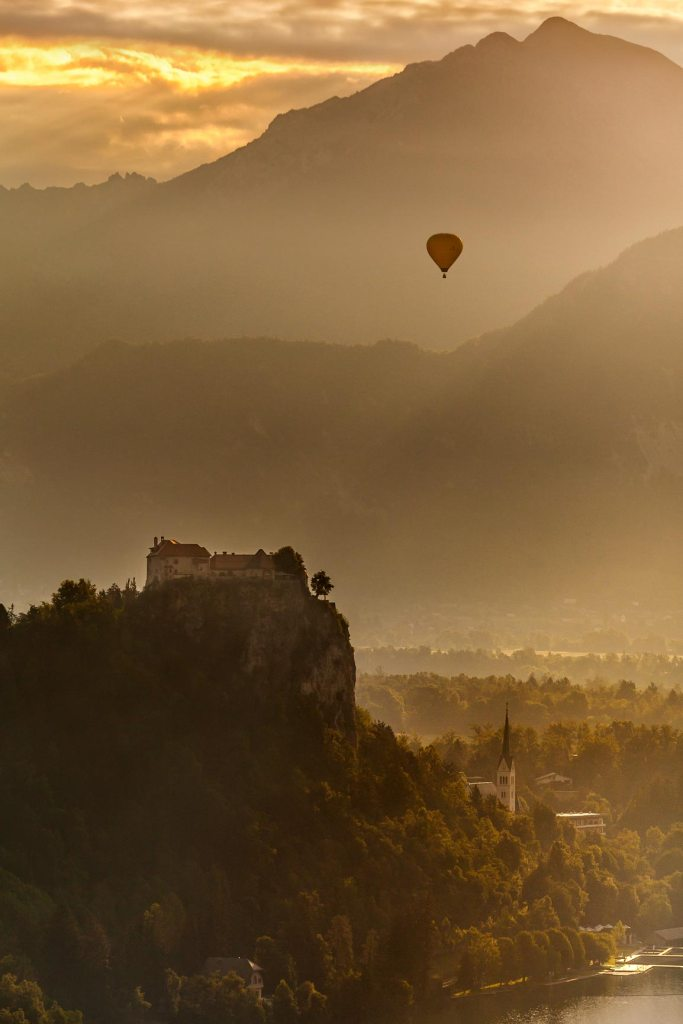Hot air balloon flying over lake Bled
