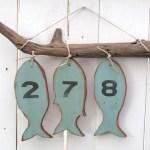 Números de endereço para casa de praia com peixes de madeira