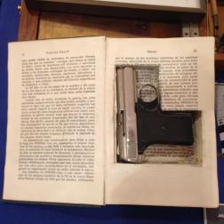 Pistola camuflada en el interior de un libro
