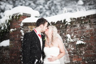 Mat Smith Photography - Nikki and Tom kiss in the snow outside Ye Olde Bell, Hurley Village