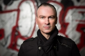 Headshot of man in black army style coat in front of red and white graffiti